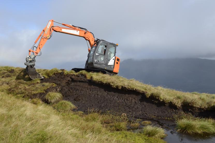 Peatland Action – digger re-profiling bare peat hag.