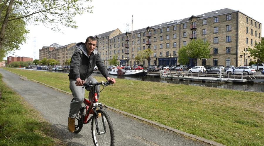 Person cycling along a Green Infrastructure project site by the Forth and Clyde canal in Glasgow. ©Lorne Gill/SNH. For information on reproduction rights contact the Scottish Natural Heritage Image Library on Tel. 01738 444177 or www.nature.scot