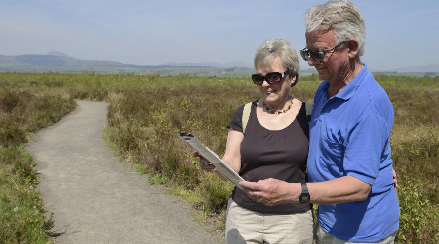 Margaret & Danny Dyball reading the leaflet about raised bogs on a walk on the trail at Flanders Moss NNR. ©Lorne Gill/SNH. For information on reproduction rights contact the Scottish Natural Heritage Image Library on Tel 01738 444177 or www.nature.scot
