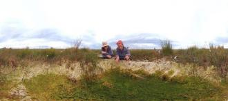 Two people looking at a bog pool discussing the merits peat bogs have in tacking climate change. Credit: still taken from 360 VR film funded by SEFARI - https://sefari.scot/ . Directed and filmed by Andrew Macdonald of Exhibit Scotland.