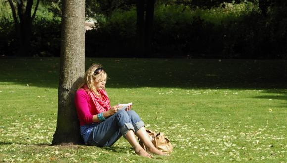 Young woman sitting under a tree reading in Kelvingrove Park, Glasgow. ©Lorne Gill/SNH. For information on reproduction rights contact the Scottish Natural Heritage Image Library on Tel. 01738 444177 or www.nature.scot