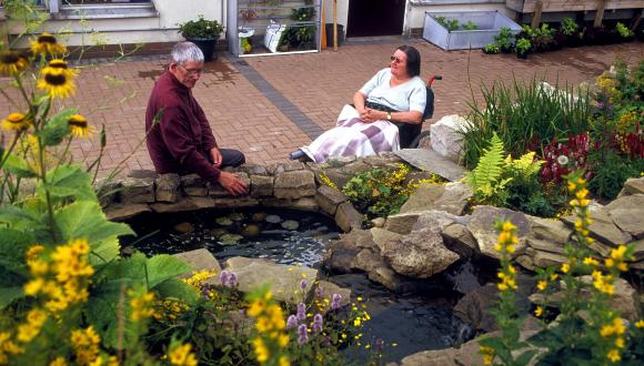 People relaxing by the pond in The Thistle Foundation community garden, Edinburgh ©George Logan/SNH. For information on reproduction rights contact the Scottish Natural Heritage Image Library on Tel. 01738 444177 or www.nature.scot