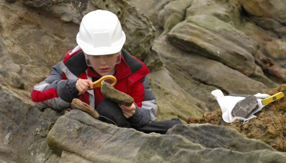 Young geologist preparing fossils on a rocky shore, St.Andrews, Forth and Borders Area. ©Lorne Gill/SNH. For information on reproduction rights contact the Scottish Natural Heritage Image Library on Tel. 01738 444177 or www.nature.scot