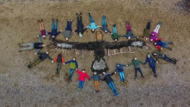 Group of children holding hands laying on the ground in a circle